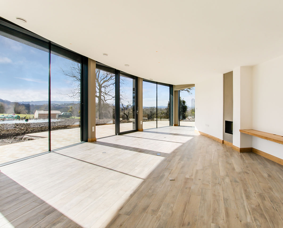 The glazed lounge at Headlands, a large Para 55 family home in Prestbury. Designed by Hawkes Architecture, this energy efficient timber-frame passivhaus utilises the latest renewable technology.