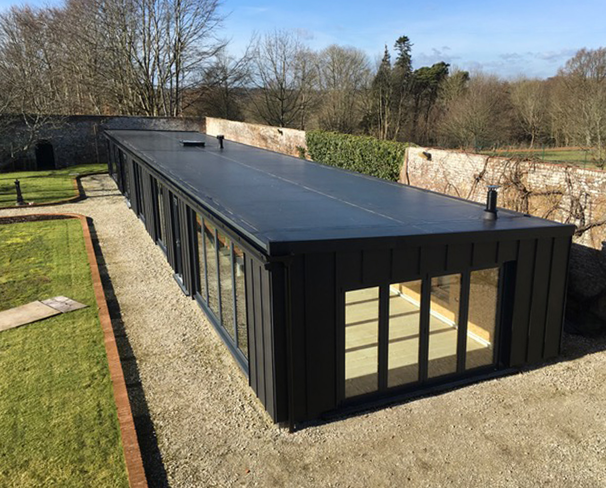 Exterior of Walled garden, an energy efficient, self-built pavilion building, constructed inside the walls of a grade II listed walled garden and designed by Hawkes Architecture.
