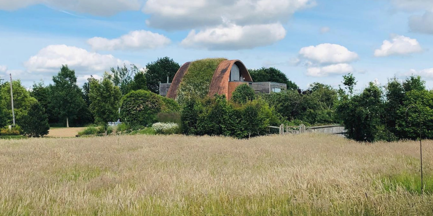 Meadow view of Crossway's parabolic timber vaulted arch. Crossway is a PPS 7 Passivhaus that featured on Grand Designs.